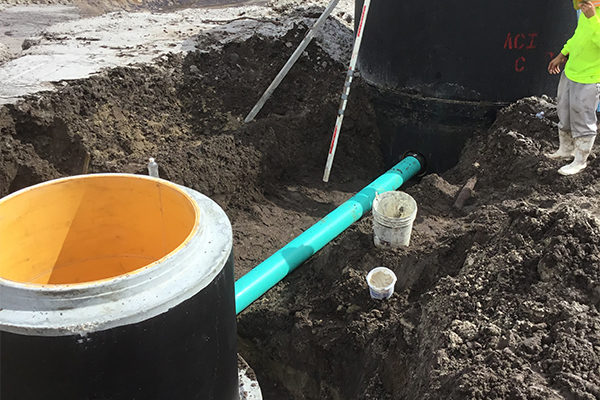 Base and riser section are in place. Pipe layed between well and collection manhole.