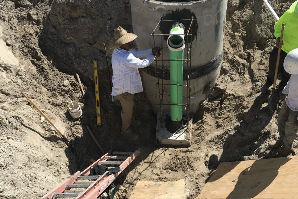 For shallow pipes entering a deep structure most specs call for building an extensive outside drop assembly encased in concrete.